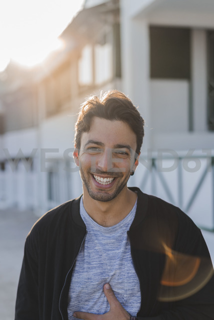 Portrait of laughing young man on the beach at sunset - AFVF00134