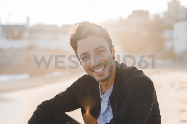 Portrait of smiling young man sitting on the beach at sunset - AFVF00137