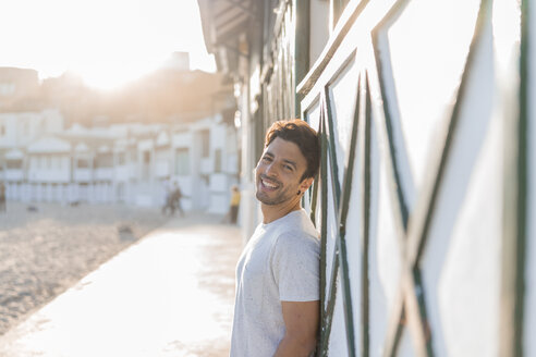 Portrait of happy young man on the beach at sunset - AFVF00140