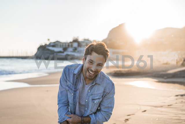 Portrait of laughing young man on the beach at sunset - AFVF00146