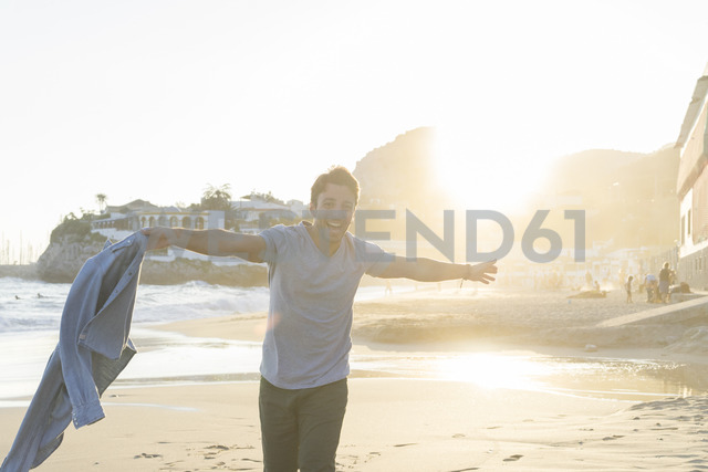 Portrait of happy young man dancing on the beach at sunset - AFVF00149