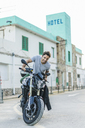 Portrait of happy young man with motorbike - AFVF00155