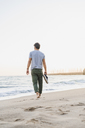 Back view of man walking barefoot on the beach - AFVF00158