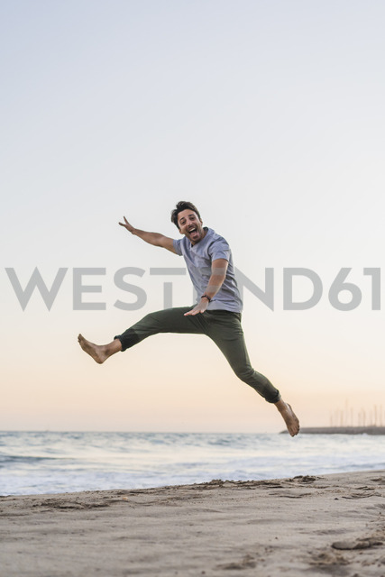 Happy young man jumping in the air on the beach at sunset - AFVF00161