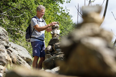 Italy, South Tyrol, Vinschgau, Naturns, Sonnenberg Panorama Trail, hiker and cairn - LBF01782