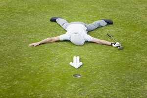 A golfer lying on a putting green behind an arrow of golf balls - FSIF02643