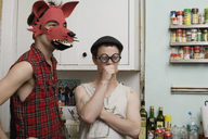 Two young men standing in a kitchen wearing silly disguises - FSIF02658
