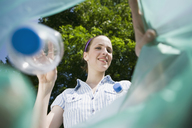 A woman throwing a plastic bottle away - FSIF02691