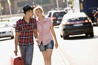 A young couple walking with a suitcase - FSIF02739