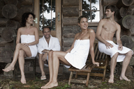 Four people relaxing outside the sauna at a health spa - FSIF02745