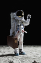 An astronaut on the moon carrying a suitcase and waving - FSIF02766