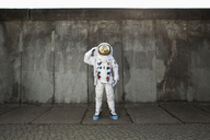 A saluting astronaut standing on a sidewalk in a city - FSIF02769