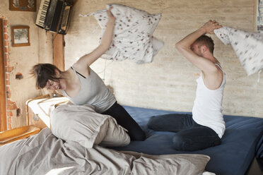A boyfriend and his girlfriend having a pillow fight in bed - FSIF02775