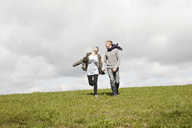 A couple running down a hill while holding hands - FSIF02778