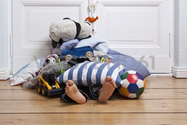A child covered in toys, only feet visible - FSIF02823 - fStop/Westend61