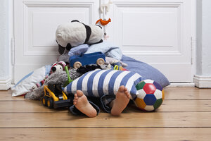 A child covered in toys, only feet visible - FSIF02823