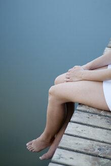 Woman sitting on pier - FSIF02831