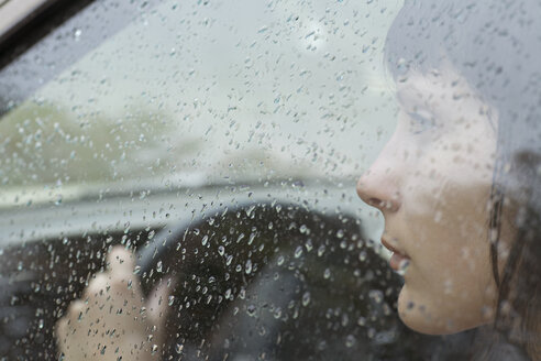 A woman driver sitting in car looking out window, raindrops on window - FSIF02876