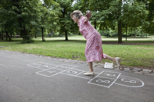 Senior woman playing hopscotch - FSIF02879