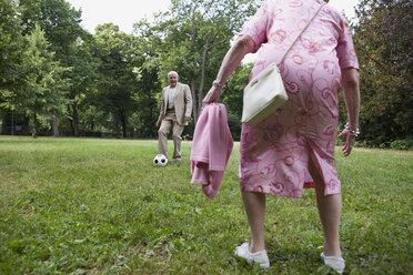 Senior couple play soccer in the park - FSIF02885