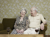 Senior couple relaxed on couch with two glasses of wine on the table - FSIF02888