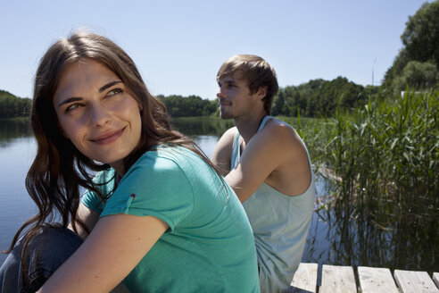 Couple side by side on jetty with girl looking very happy - FSIF02891