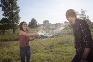Girl sprays guy with hose in a field - FSIF02897
