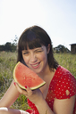 Girl sitting in field with a slice of melon in her hand - FSIF02903