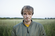 Profile of man standing in secluded field with cigarette hanging out of his mouth - FSIF02909