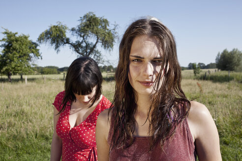 Two cool girls standing in field with one looking at camera - FSIF02912