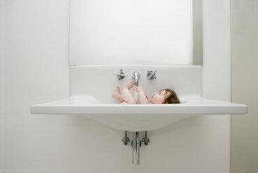 A baby taking a bath in sink - FSIF02915