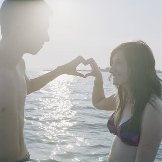 A young couple making a heart sign with their hands - FSIF02933