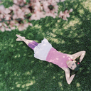A teenage girl lying in grass with hands behind head, looking up - FSIF02936