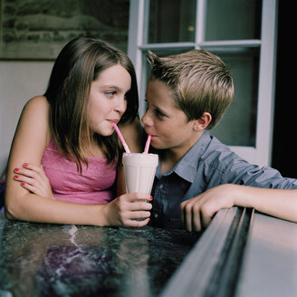 A young teenage couple sharing a milkshake at a diner - FSIF02939