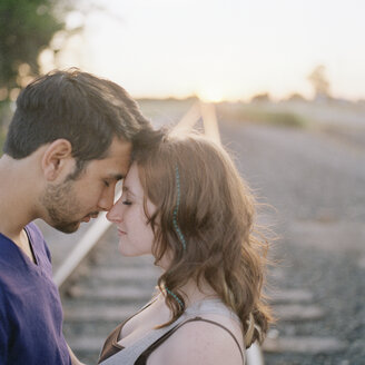 A young couple touching foreheads near railroad track - FSIF02948