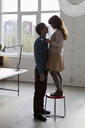 A young woman standing on a stool facing her tall boyfriend - FSIF02957
