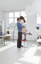 A woman standing on a stool with her arms around her boyfriend - FSIF02960