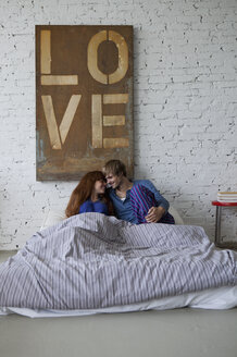 A young grinning couple in bed preparing to kiss - FSIF02969