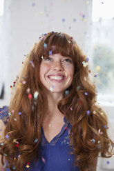 A smiling woman looking up at confetti falling - FSIF02972
