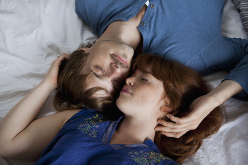 A young couple lying head to head on a bed, eyes closed - FSIF02978
