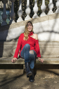 Laughing young woman sitting on bench in a public garden - AFVF00179