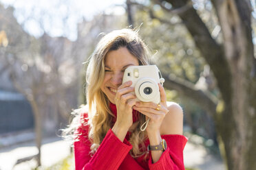 Happy young woman taking a picture in a garden - AFVF00185