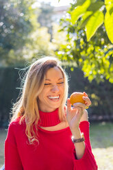 Laughing young woman holding mandarin in a garden - AFVF00194