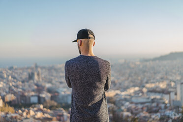 Spain, Barcelona, young man standing on a hill overlooking the city - AFVF00202