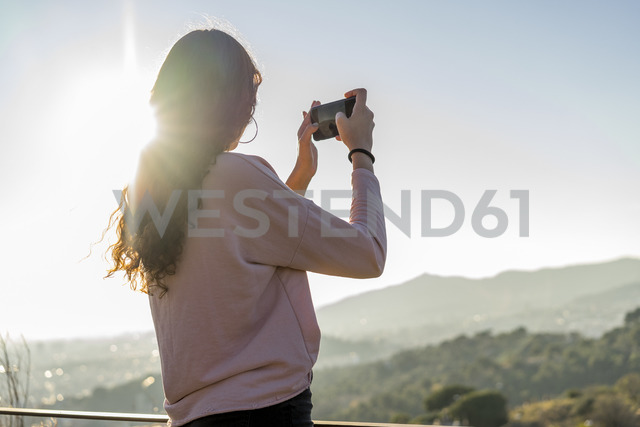 Young woman standing on a hill taking cell phone picture - AFVF00211
