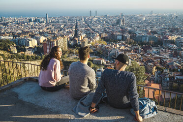 Spain, Barcelona, three friends sitting on a wall overlooking the city - AFVF00217