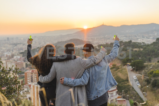 Spain, Barcelona, three friends with beer bottles embracing on a hill overlooking the city at sunset - AFVF00223
