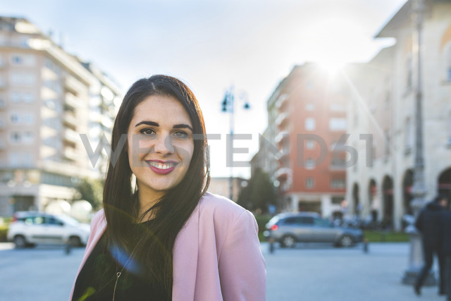 Portrait of smiling young woman in the city - WPEF00143