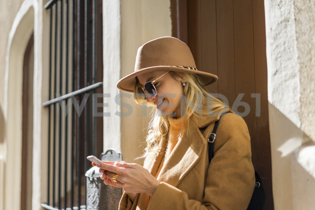 Fashionable young woman at house entrance using cell phone - AFVF00229