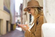 Fashionable young woman in a lane using cell phone - AFVF00232